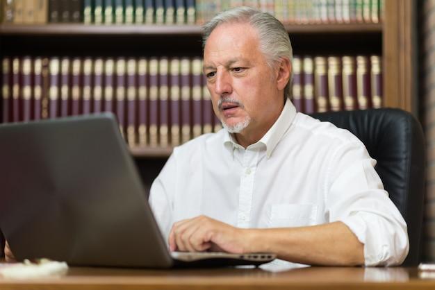 Zakenman die zijn laptop in een bibliotheek met behulp van