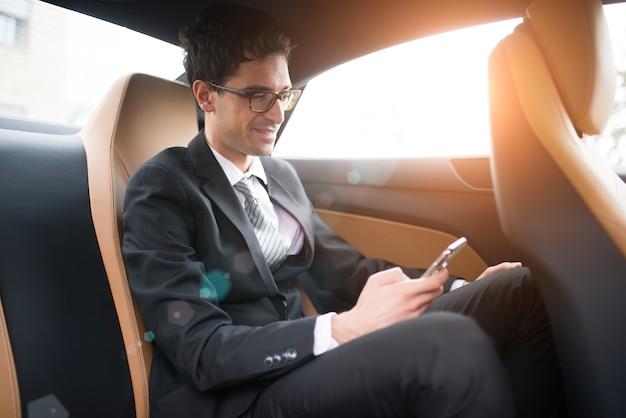Zakenman die zijn mobiele telefoon in de achterbank van een auto met behulp van