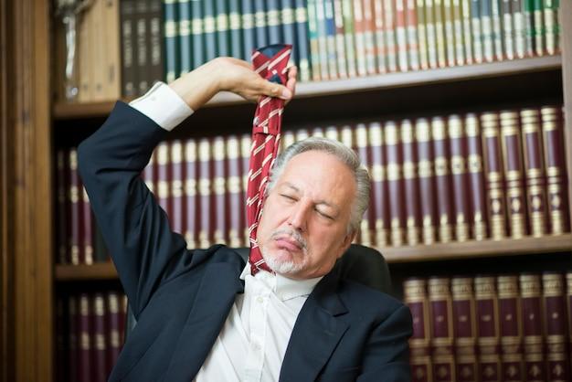 Zakenman die zijn stropdas houdt om op te hangen