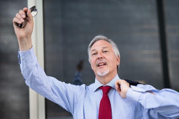 Zakenman die zijn vinger opsteekt om een taxi buiten in een stad te bellen