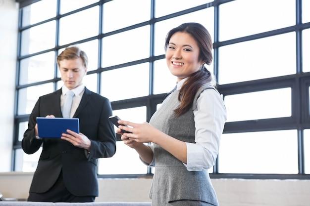 Zakenman digitale tablet gebruiken en onderneemster die mobiele telefoon in het bureau met behulp van