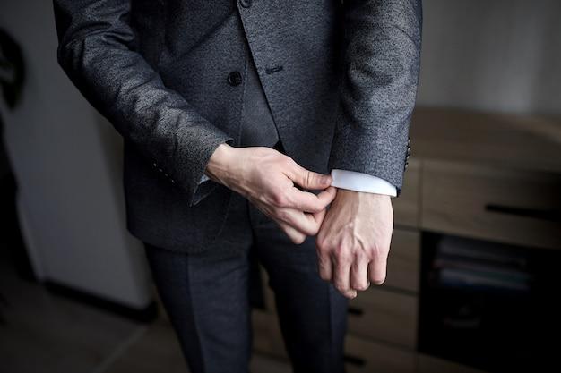 Zakenman draagt een jas, mannelijke handen close-up, bruidegom maakt zich klaar in de ochtend voor de huwelijksceremonie