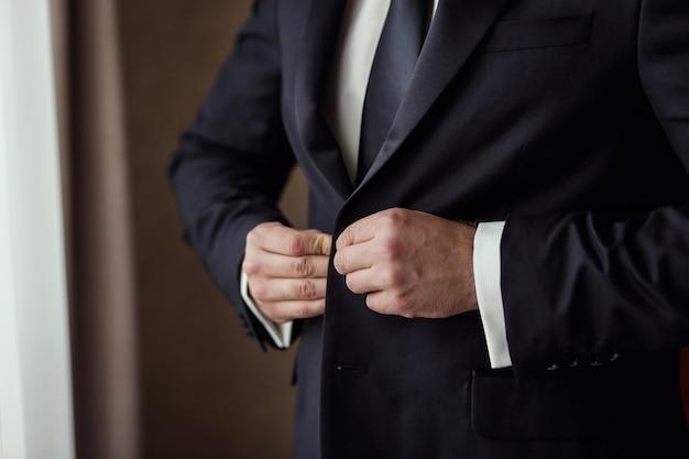 Zakenman draagt een jasje. politicus, man's stijl, mannelijke handen close-up, amerikaanse, europese zakenman, business, mode en kleding concept