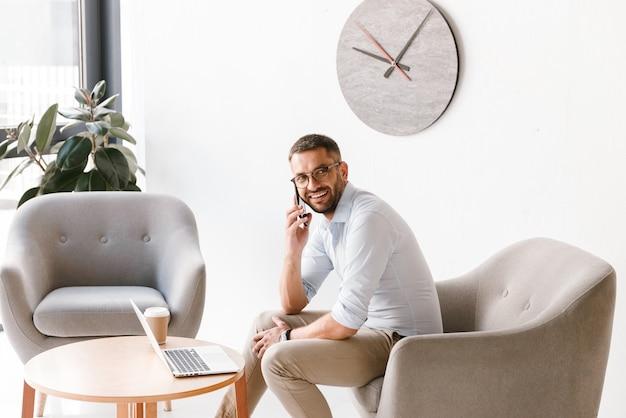 Zakenman dragen van stijlvolle formele kleding, zittend in een stoel en bezig met laptop in kantoor interieur, tijdens het gesprek op de mobiele telefoon