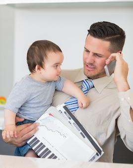 Zakenman dragende baby en documenten terwijl op oproep
