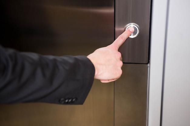 Zakenman dringende liftknop in kantoor
