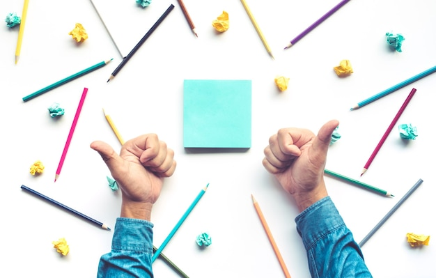 Zakenman duim omhoog hand voor vieren idee met potlood en briefpapier op witte tafel. zakelijke creativiteit en onderwijsconcepten