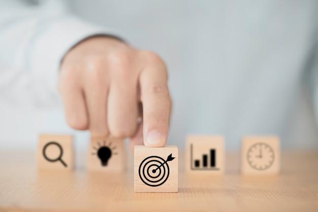 Zakenman duwen doelpictogram dartbord voor anderen pictogrammen om bedrijfsdoelstellingen in te stellen