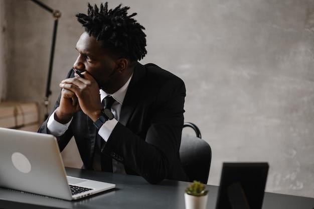 Zakenman een afro-amerikaanse man in een pak werkt op een laptop