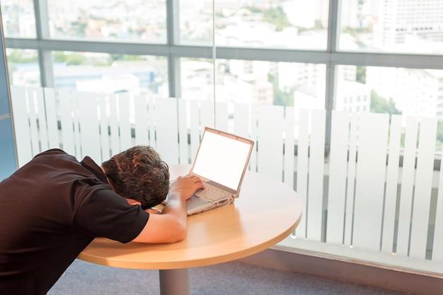 Zakenman. een dutje doen, moe van het werk, slapen voor de laptop, liggend op zijn handen.