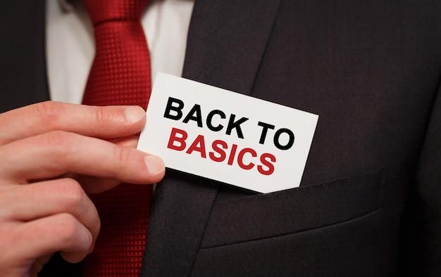 Zakenman een kaart met tekst back to basics in de zak steken