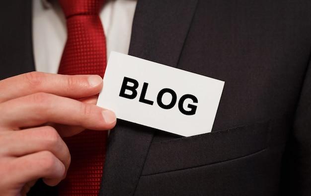 Zakenman een kaart met tekst blog in de zak zetten