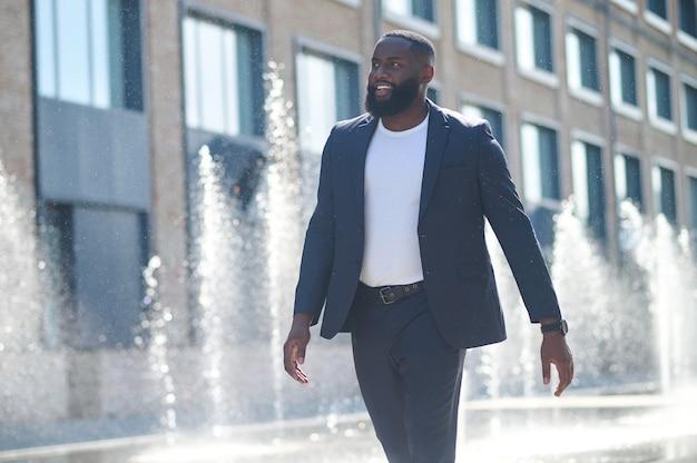 Zakenman. een lange man met een donkere huidskleur in een pak op straat