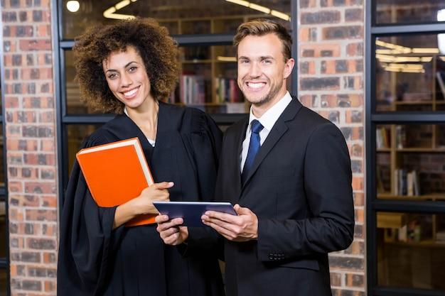 Zakenman en advocaat die zich dichtbij bibliotheek met digitaal tablet en wetsboek bevinden