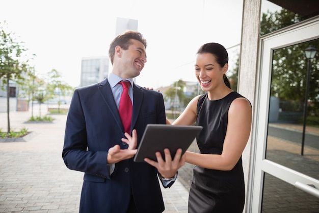 Zakenman en collega bespreken over digitale tablet en lachen