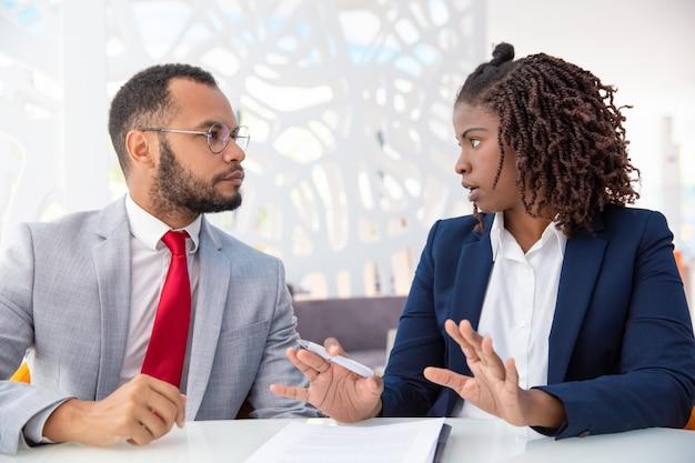 Zakenman en onderneemster die contract bespreken