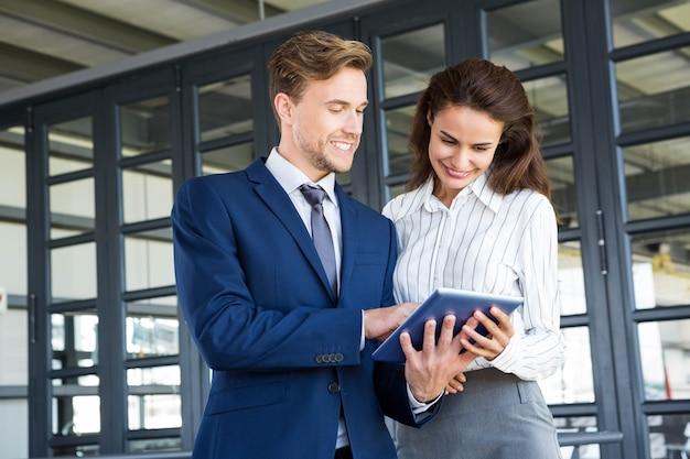 Zakenman en onderneemster die digitale tablet in bureau gebruiken