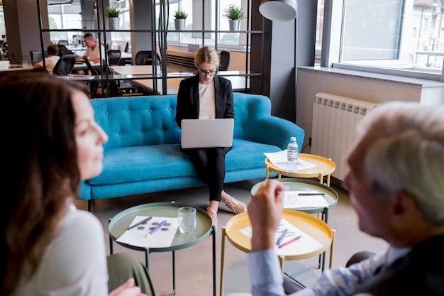 Zakenman en onderneemster die elkaar voor jonge vrouw bekijken die laptop met behulp van