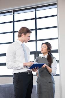 Zakenman en onderneemster die gebruikend digitale tablet in het bureau op elkaar inwerken
