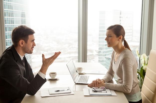 Zakenman en onderneemster die het werk bespreken bij bureau