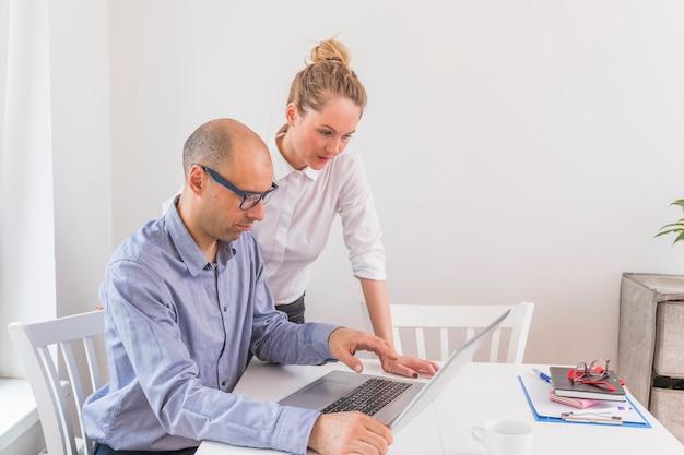 Zakenman en onderneemster die laptop bekijken