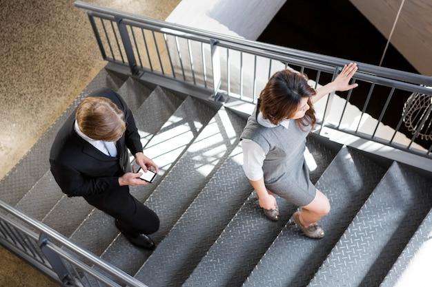 Zakenman en onderneemster die trap in bureau beklimmen