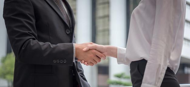Zakenman en onderneemsterschokhand voor het succes van het overeenkomstenconcept