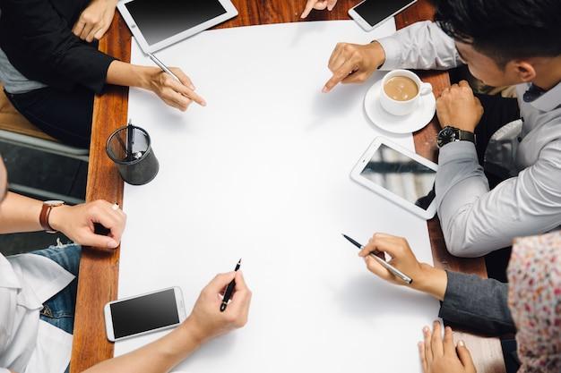 Zakenman en onderneemsterzitting in koffie die iets op papier bespreken