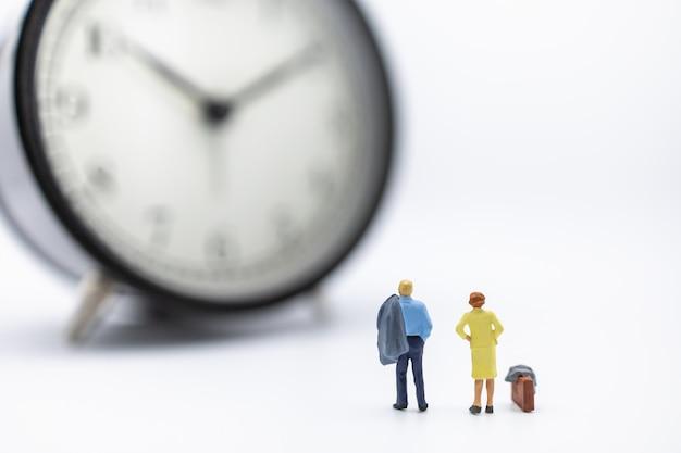 Zakenman en vrouwen miniatuurcijfer die en zich aan uitstekende ronde klok op wit bevinden kijken.