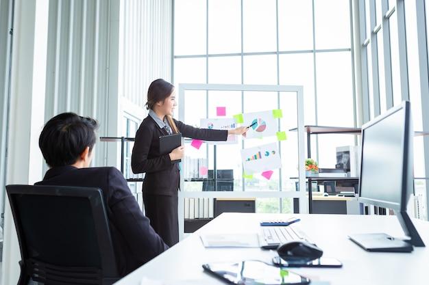 Zakenman en zakenvrouw baas twee partners presenteren nieuwe projectideeën en de toename van ontvangen armbanden in kantoor, vrouwelijke coach presenteren succesvol businessplan