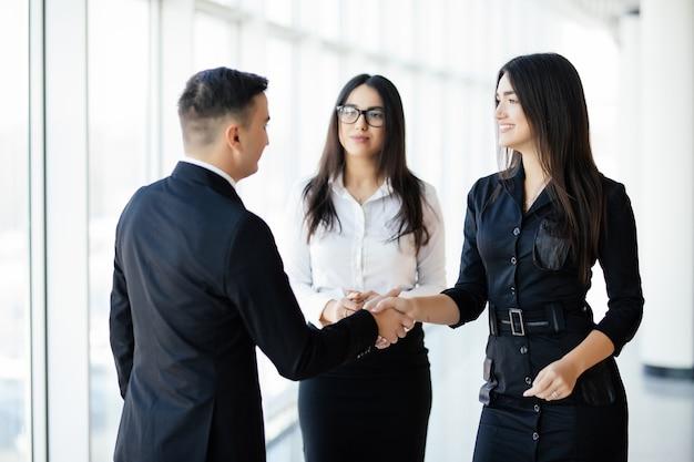 Zakenman en zakenvrouw handen schudden in de hal van het kantoor op informele bijeenkomst