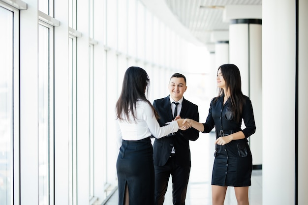 Zakenman en zakenvrouw handen schudden in de hal van het kantoor op informele bijeenkomst Premium Foto