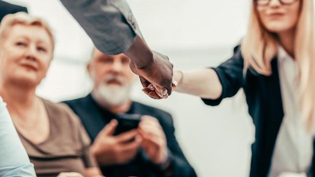 Zakenman en zakenvrouw handen schudden over de vergadertafel. bedrijfsconcept