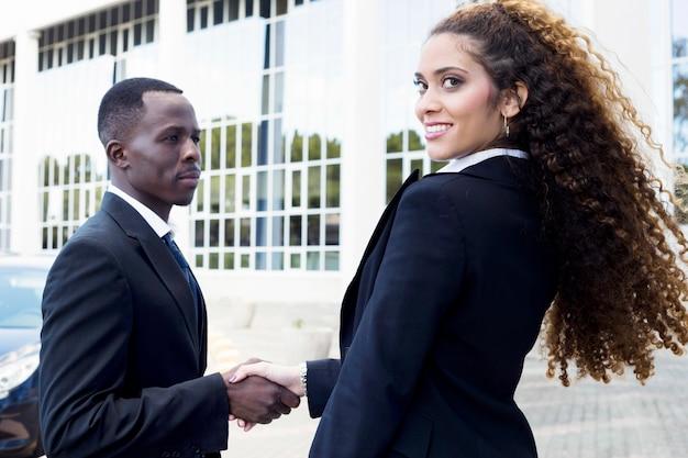 Zakenman en zakenvrouw handen schudden
