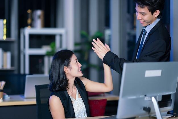 Zakenman en zakenvrouw houden hand samen in kantoornacht