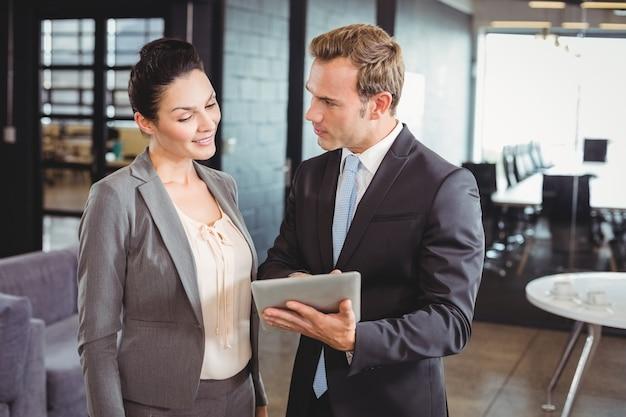Zakenman en zakenvrouw met behulp van digitale tablet