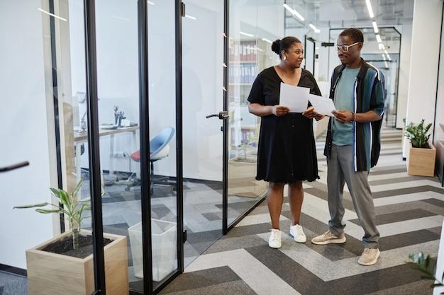 Zakenman en zakenvrouw met gedrukte rapporten staan in kantoorgangen en bespreken verkoop...