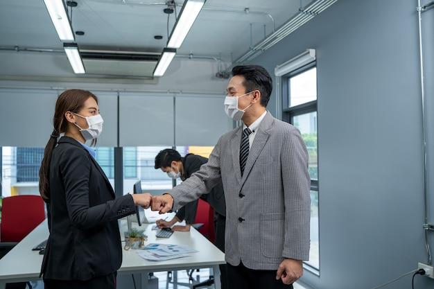 Zakenman en zakenvrouw met medisch masker in kantoor na covid-19 quarantaine en lockdown.