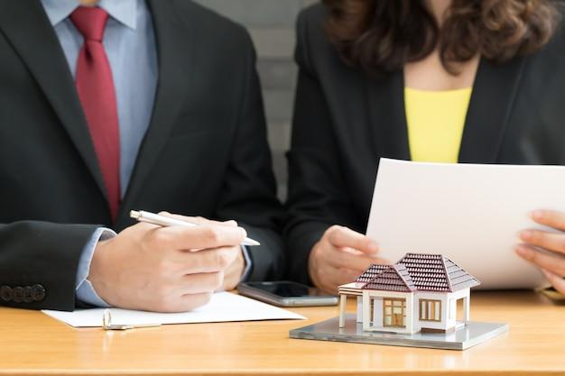Zakenman en zakenvrouw ondertekenen van een contract voor investeringen in onroerend goed