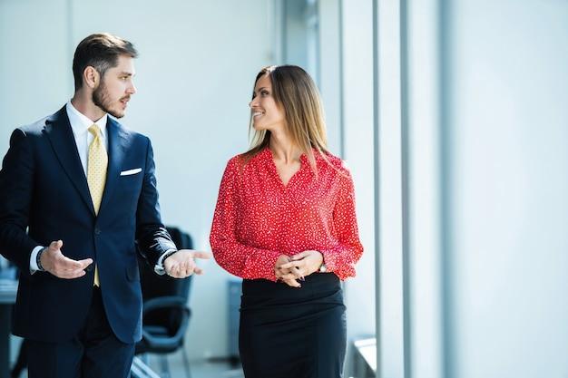 Zakenman en zakenvrouw praten tijdens het wandelen in moderne kantoren
