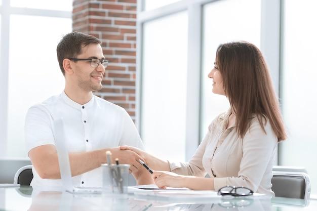 Zakenman en zakenvrouw schudden handen terwijl ze aan de balie zitten. concept van samenwerking