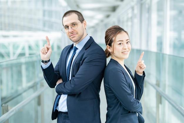 Zakenman en zakenvrouw staan rug aan rug in het gebouw