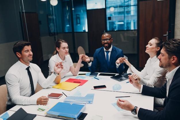 Zakenman en zakenvrouw team mediteren en houden elkaar de hand na kantoorvergadering zakelijke...