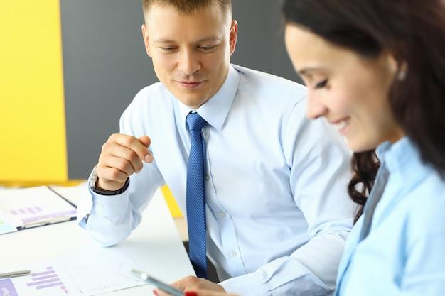 Zakenman en zakenvrouw zitten in kantoor aan tafel en kijken naar smartphone.