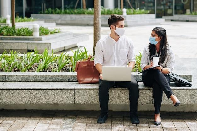 Zakenman en zakenvrouw zittend op een bankje in medische maskers en kijken elkaar aan bij het bespreken van werk