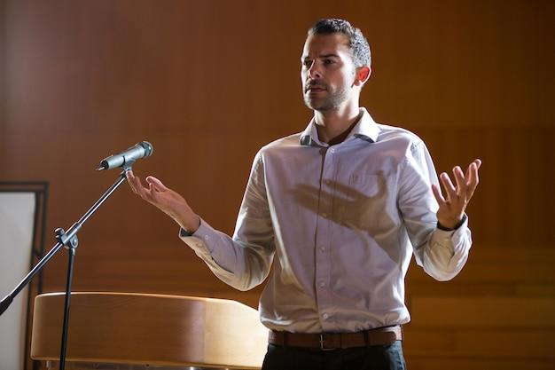 Zakenman gebaren terwijl hij een toespraak houdt in het conferentiecentrum