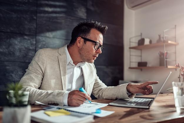 Zakenman gebruikend laptop en benadrukkend tekst in zijn bureau