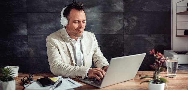 Zakenman gebruikend laptop en luisterend muziek op hoofdtelefoons