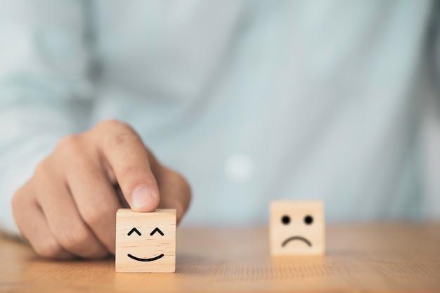 Zakenman gebruikt vinger om glimlachgezicht te wijzen dat het scherm op houten kubusblok, emotie en mentaliteitsconcept afdrukt.
