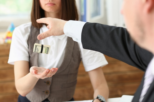 Zakenman geeft een kotelet van geld aan een vrouw in de vorm van een salaris omkopen in een envelop dollar equivalent